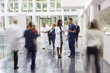 Stock photo of busy hospital staff walking through a hallway.